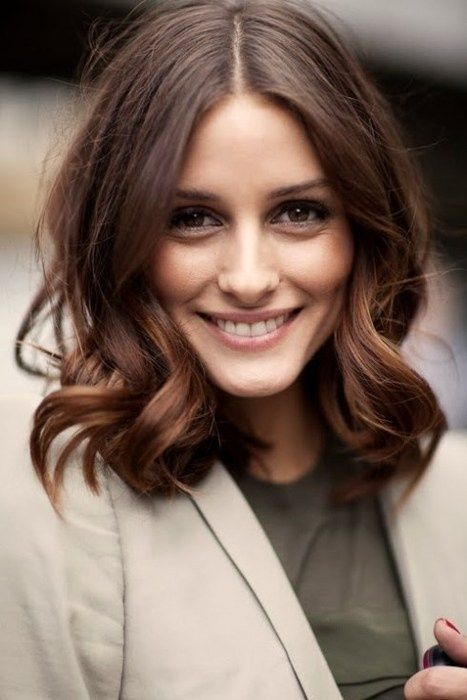 Flattering for oval, oblong and triangular faces, a symmetric centre-parted haircut with fluffy curls on the sides of the face is an awesomely-looking and easily-styled solution.