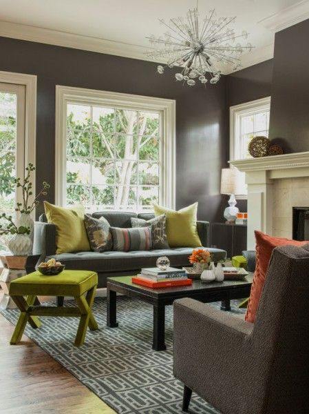 a charcoal gray transitional seating area with pops of bright orange and green, a tufted sofa, upholstered x-leg ottoman and patterned rug