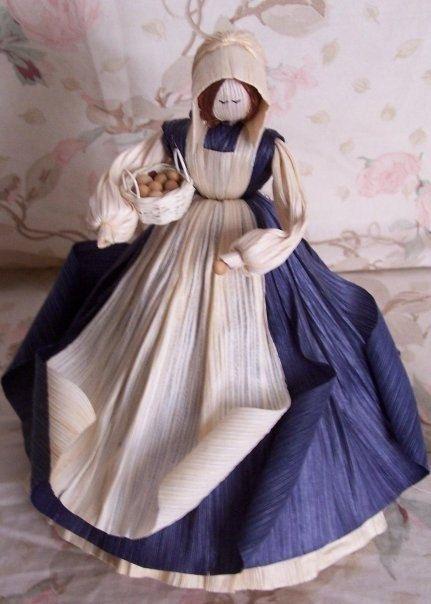 La señora del huevo azul con capucha con pelo largo seda de maíz del país. Sosteniendo una cesta de huevos también con uno. Individualmente