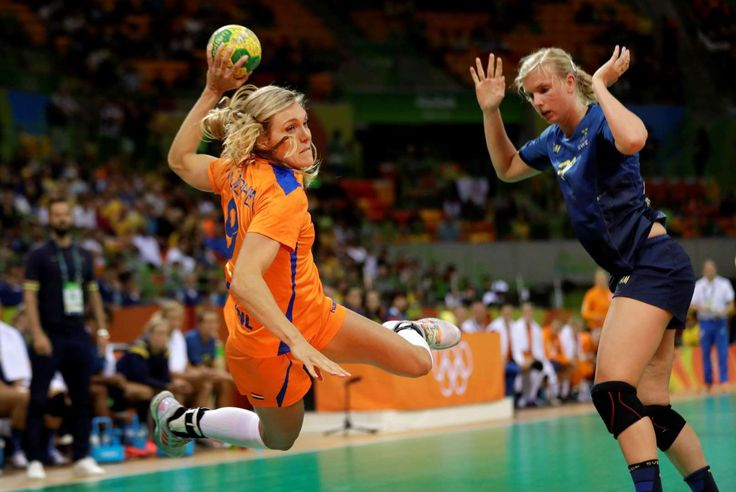 She shoots, she scores: The Netherlands' Sanne Van Olphen, left, scores a goal past Sweden's Jenny Alm during their preliminary handball match on Aug. 12.