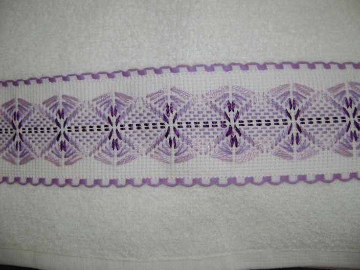 Una segunda toallita facial del juego de 3 bordadas con cenefá de cuadrillé en morado, a puntada yugoslavo