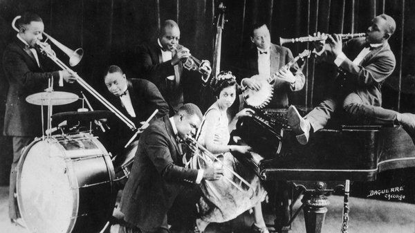 Paramount Chair Co. - Paramount Records King Oliver's Creole Jazz Band in Chicago in 1923: Louis Armstrong is kneeling, from left to right behind him are Honore Dutrey, Baby Dodds, King Oliver, Lil Hardin, Bill Johnson and Johnny Dodds.