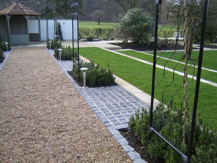 Stabilised golden gravel garden path with dark grey granite setts
