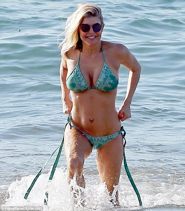 So fit: The star couldn't have looked happier to show off all the results of her training as she strolled on the beach in a skimpy green bikini with long, side-ties