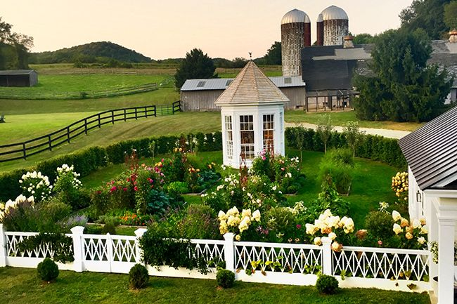 """The garden at Clove Brook Farm was designed by P. Allen Smith in collaboration with potter Christopher Spitzmiller in 2014. It was design to complement the 1830's Greek Revival farm house, complete with a custom fence, inspired by the balustrade on the Louisiana Plantation """"Felicity"""" in the movie 12 Years A Slave. The garden, planted in 2014, sprung from the earth with great gusto and was inspired by the many visits to the garden of close friend Bunny Williams. The"""