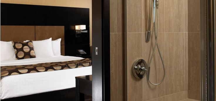 Shower area at Turtle Creek Casino & Hotel -  Junior Suite Well over 300 square feet of casual contemporary elegance. Provides King beds covered in crisp white linen, plus a sofa-sleeper. Bathroom counter-tops are golden amber granite. Oversized shower features seating and multiple shower-heads. Includes 37-inch LCD television, plus an easy-to-set Sharper Image Perfect Hotel Alarm Clock with iPod/MP3 Player Docking Alarm Clock.