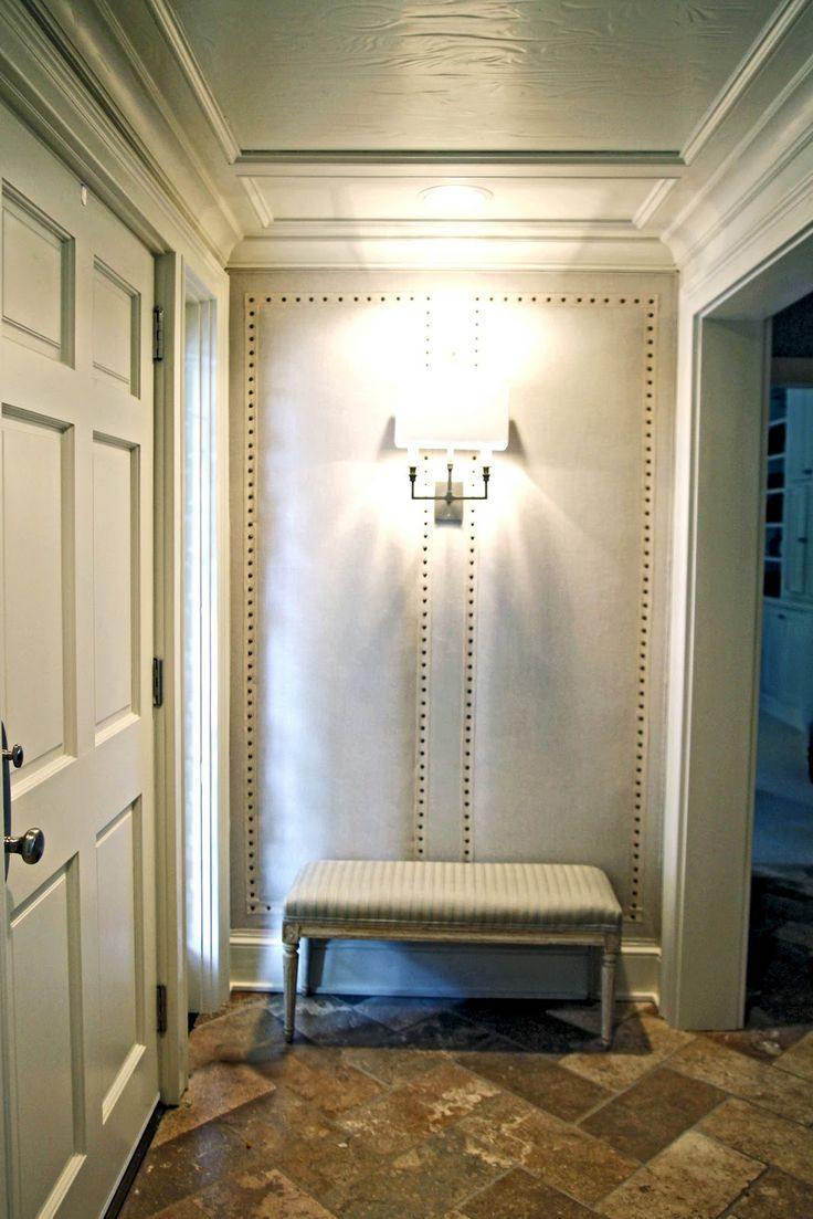 Upholstered entry wall with nailhead trim.
