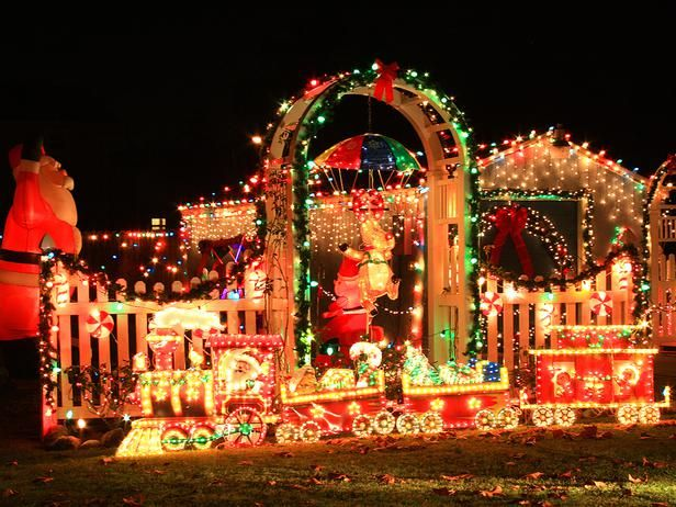 Covered in colored lights and garland, this fenced-in yard makes a bold and festive statement with a giant inflatable Santa Claus, miniature Polar Express and decorative yard accessories.: Color Schemes, Christmas Wonderland, Christmas Displays, Christmas Theme, Christmas Lights Peace, Christmas Training, Christmas Outdoor, Christmas Yard, Outdoor Christmas