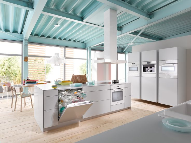 High ceilings, floor to ceiling windows, all white cupboards and Miele Generation 6000 PureLine appliances in Brilliant White lends a feeling of airy spacious to this open plan kitchen #kitchendesign