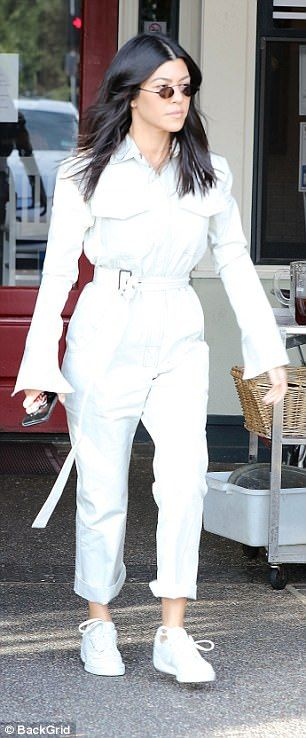 Stunning: The 38-year-old doting mom looked chic in white trousers with a coat, adding matching sneakers