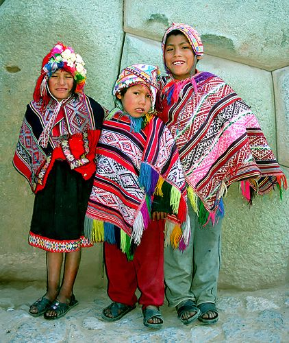 peruvian kids wearing traditional ponchos and hats