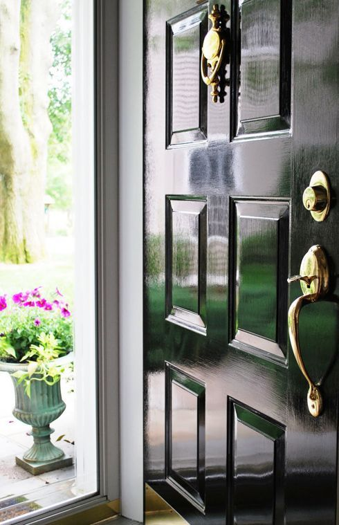 glossy black front door - love- this is the exact door I want – from the glossy paint to the hardware and topiaries just outside!