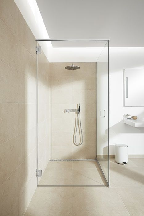 Bathroom with a stylish glass shower screen and a glass door solution with no grip. Shower with linear floor drain. Elegant grating and frame in brushed stainless steel. Unidrain® GlassLine & ClassicLine