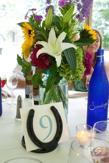 Horseshoe table numbers and mason jar centerpieces.