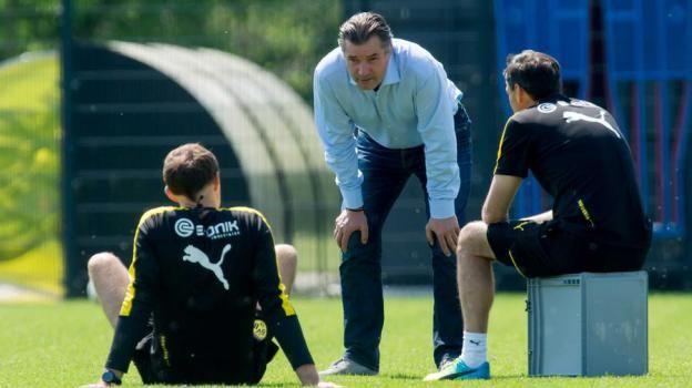 """Sportdirektor Michael Zorc (M.) im Gespräch mit Trainer Thomas Tuchel (l.) und """"Co"""" Arno Michels nach dem Training am Mittwoch."""