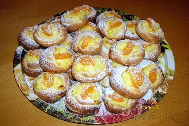 Zamotané koláčky     250 ml mléka     1 vejce     2 PL oleje     1 PL sádla     20 g másla     2 PL rumu     250 g polohrubé a 250 g hladké mouky     100 g cukru krupice     ½ lžičky citronové kůry     ½ lžičky soli     25 g droždí  Náplň:      400 ml mléka     1 vanilkový pudinkový prášek  Dále:      1 vejce na potření     kousek másla     mandarinky z kompotu     cukr na posypání