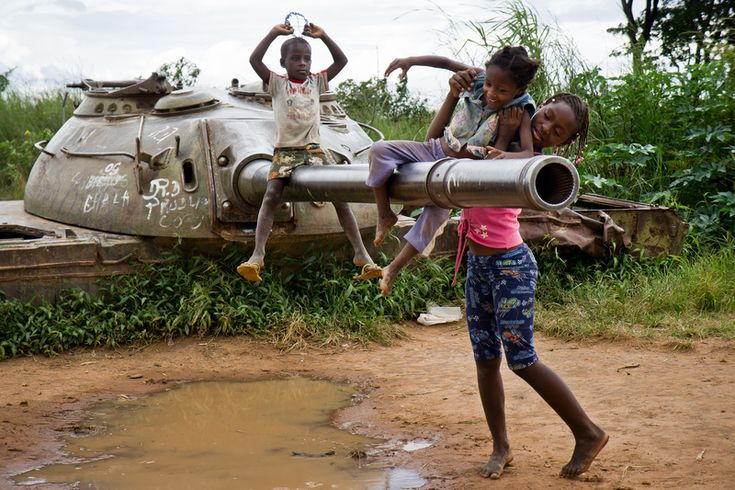 Children playing with an old abandoned tank from the Angolan Civil War in Kuito.