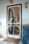 Screen door for the front door painted in a black semi gloss
