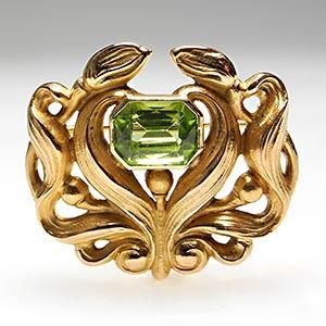 Art Nouveau at its very finest here. This brooch features ornate scroll work in 14k gold featuring an emerald-cut natural peridot gemstone.