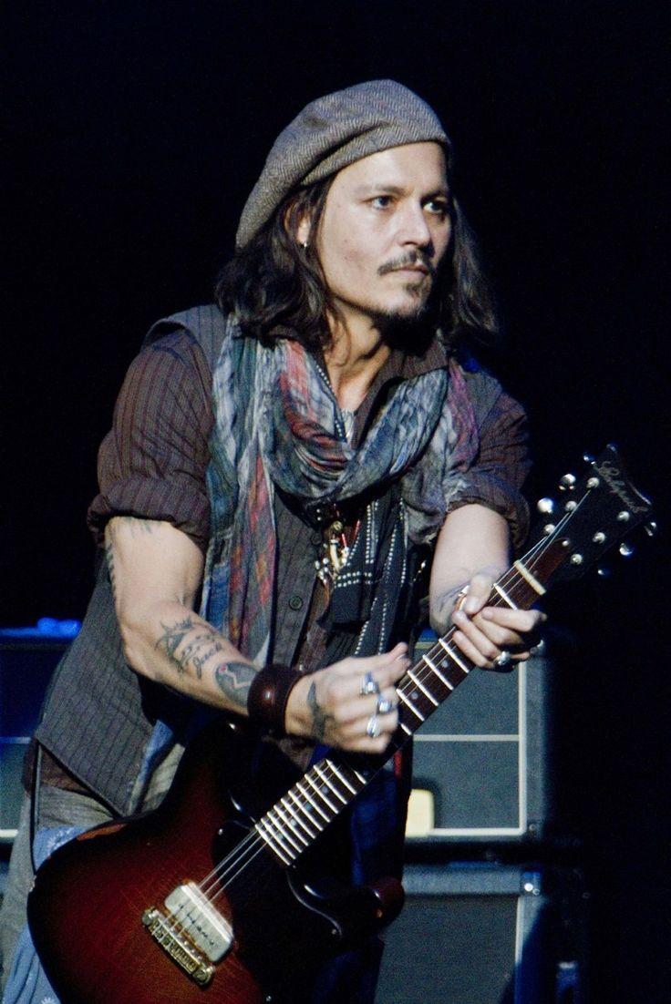 Johnny rocking a boho scarf, vest, pinstripe shirt, leather wrist wear & tweed page boy cap. Hot beyond words.