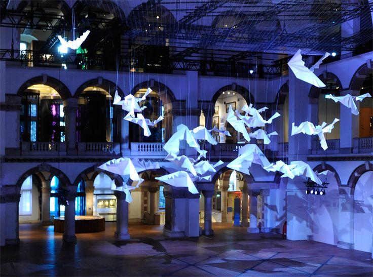 sipho mabona flocks gigantic origami birds in tropenmuseum's great hall