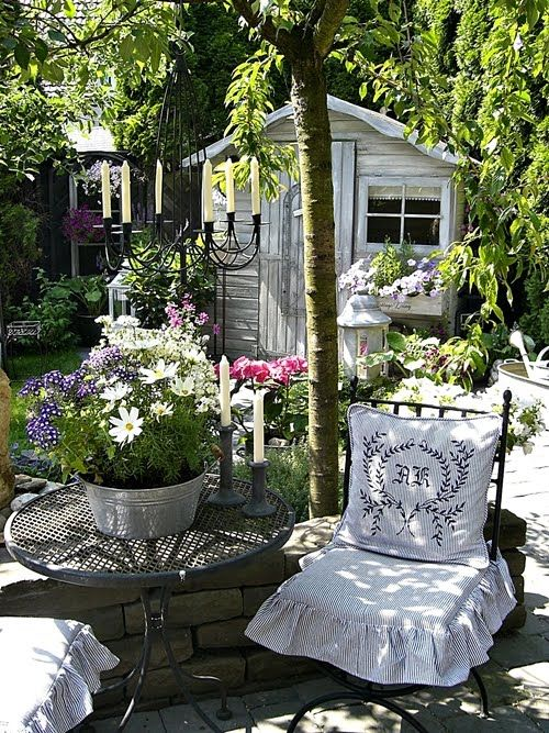 Tiny cottage/shed, pretty garden, candled chandelier and a cozy pillowed chair! Grand! | Shabbychicinspired.blogspot.com