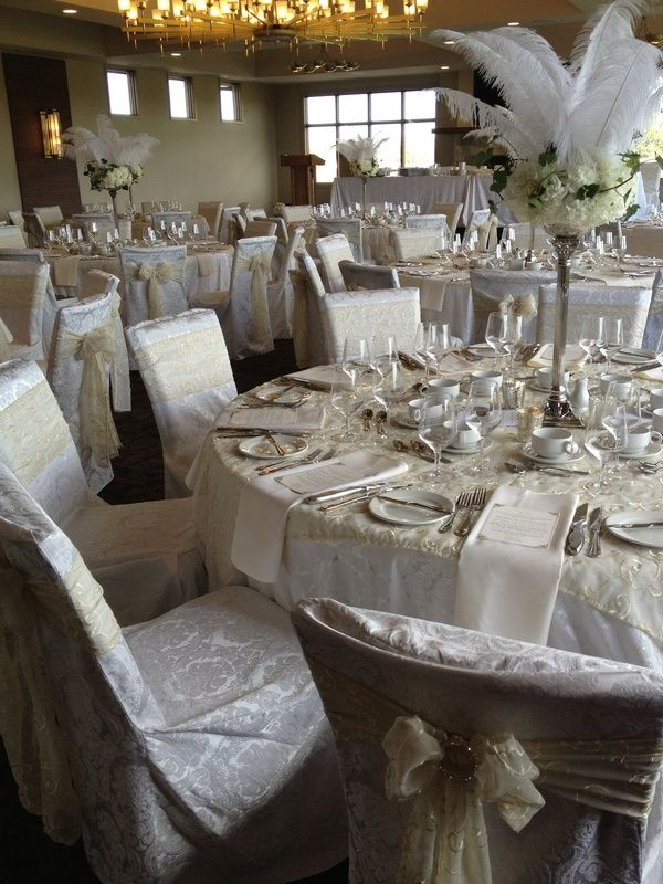 Beautiful Gatsby inspired wedding at Blue Devil Golf Course.  White damask floor length tablecloths with pale gold overlays and damask chair covers with pale gold embroidered sashes with diamond brooches.