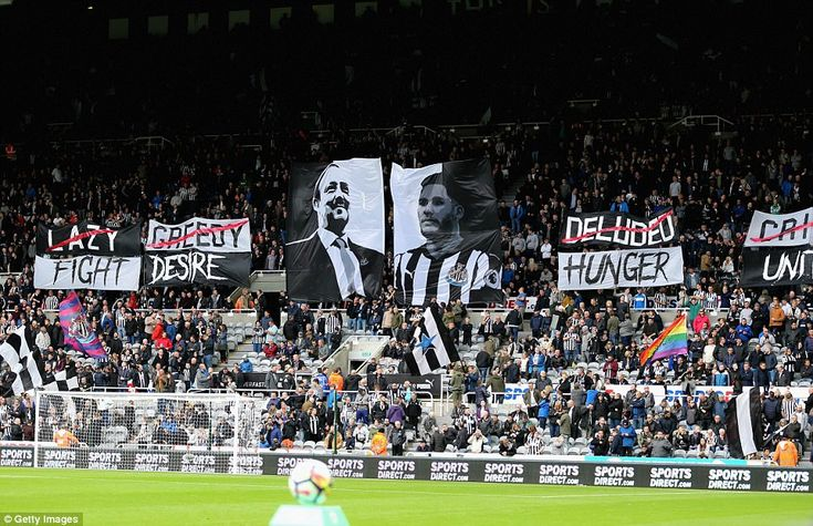 Newcastle fans show support for their team prior to the match with banners and flags, one with Rafa Benitez's face on