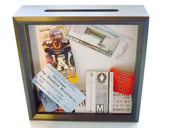 A great gift for most anyone! This drop top ticket holder has sturdy white paper in the background so that you can attach personal photos, create your own design, or leave it as it is. This shadow box makes a wonderful drop-in display frame for tickets, postcards, hotel keys, golf score cards, or anything else worth keeping and showing off!  *8 x 8 inch black shadow box *Has glass and a large slot on top *Can sit alone or hang on wall *Back comes off easily *White paper in background makes…