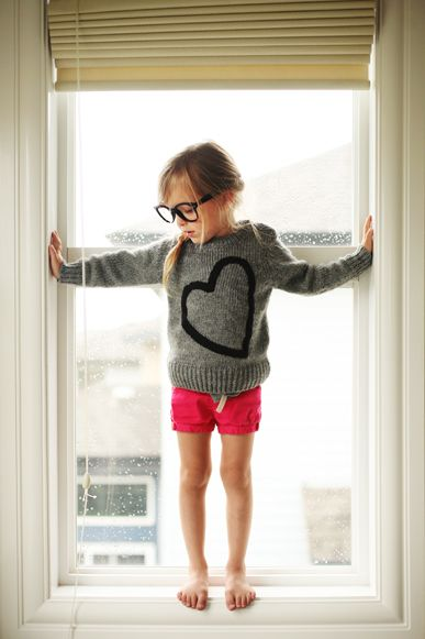 cute little girl with glasses and a heart sweater with red shorts