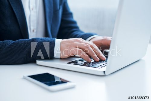 Businessman using laptop at the office. Close-up image.