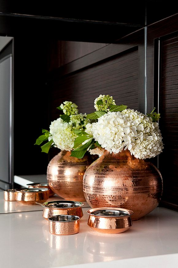 This is one of my favourite vignettes ever. The coper collection against the charcoal grey offset by the white hydrangeas are pure perfection.