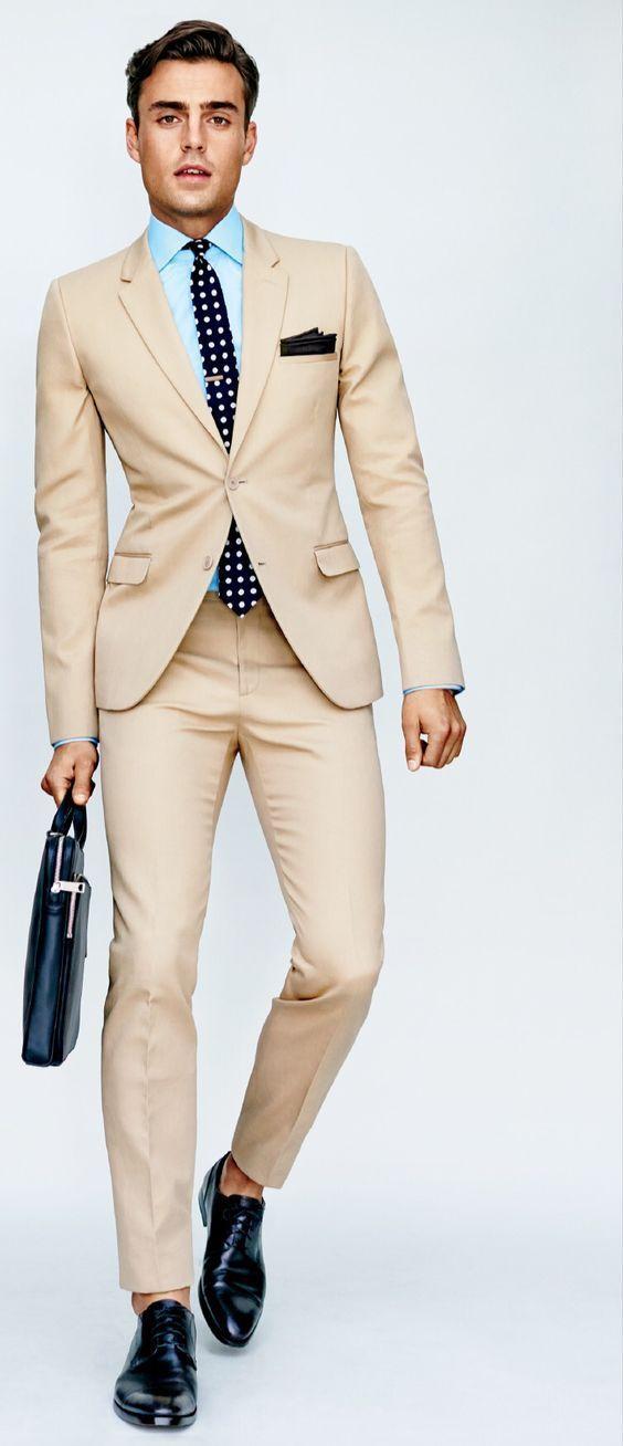 Elegante. Traje beige. Camisa azul celeste y corbata negra de lunares blancos