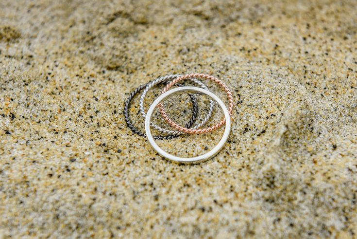 Wedding rings multiple metal on sand. Photographed by Anais Photography