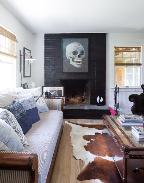 A sofa upholstered with ticking stripe paired with a steamer trunk atop a cowhide rug. #beachhouse #skulls