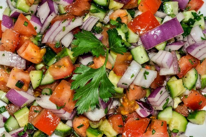 Israeli salad is the 'most well known dish of Israel' usually made of tomatoes, cucumbers, onions and parsley, dressed with fresh lemon juice and olive oil.