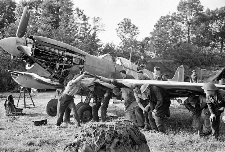 Men of an RAF Repair and Salvage Unit work on a damaged Supermarine Spitfire Mk IX of No. 403 Squadron, Royal Canadian Air Force, at a forward airstrip in Normandy, 19 June 1944. (Photo: Imperial War Museum)