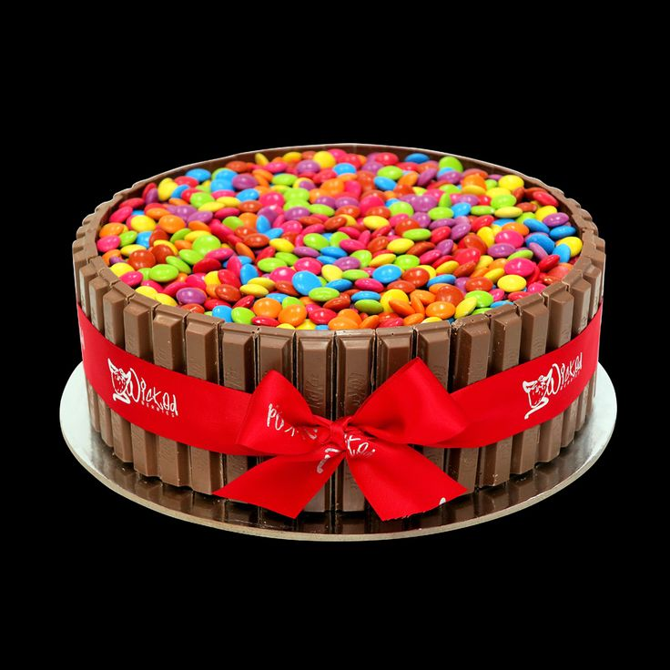 Add some colour to your party! large mudcake wrapped with Kit Kats and topped with Smarties. http://www.wickedberries.com.au
