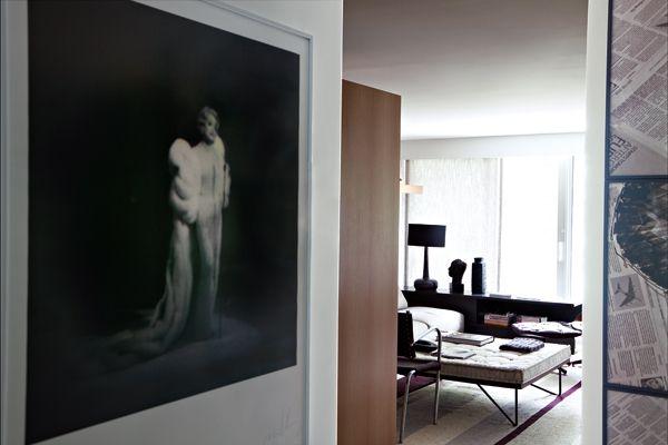 Opere di artisti brasiliani incorniciano l'ingresso del living. A sinistra, dipinto di Marcelo Paciornik; a destra, collage fotografico di Leonardo Kossoy. Nel living un divano B&B Italia, una poltrona con poggiapiedi vintage, un tappeto a motivi grafici firmato Nani Chinellato.
