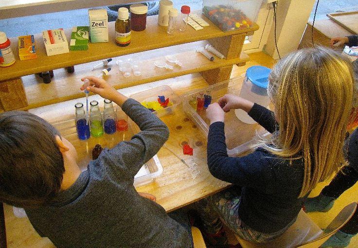 apotheek met eigen drankjes-werkplaats. Kleuren mengen met rood-geel-blauw water. Water wordt gekleurd met stukjes crêpe-papier