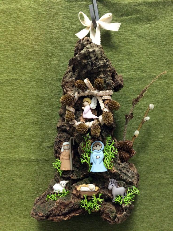 Presépio de pendurar com figuras de resina montadas numa placa de cortiça. Materiais decorativos: pau de salgueiro, vime (para a coroa) musgo artificial e fita de algodão