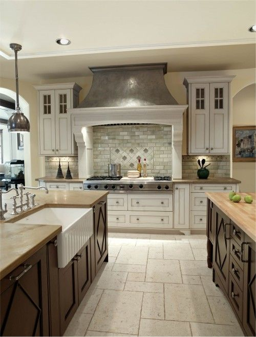 Like floor tile design, huge cook top w/ white cabinets underneath and flanking, hood. Interesting they combined dark wood cabinets in same kitchen. Sink looks cool. Loved arched doorways...