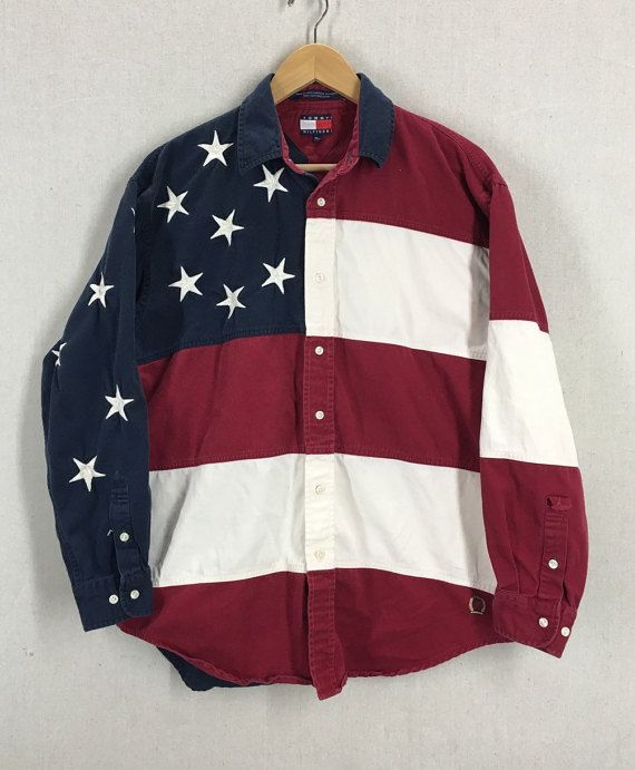 This is a Vintage Tommy Hilfiger American Flag Button Down Shirt. The tag says Size Medium - please see measurements below for better sizing.