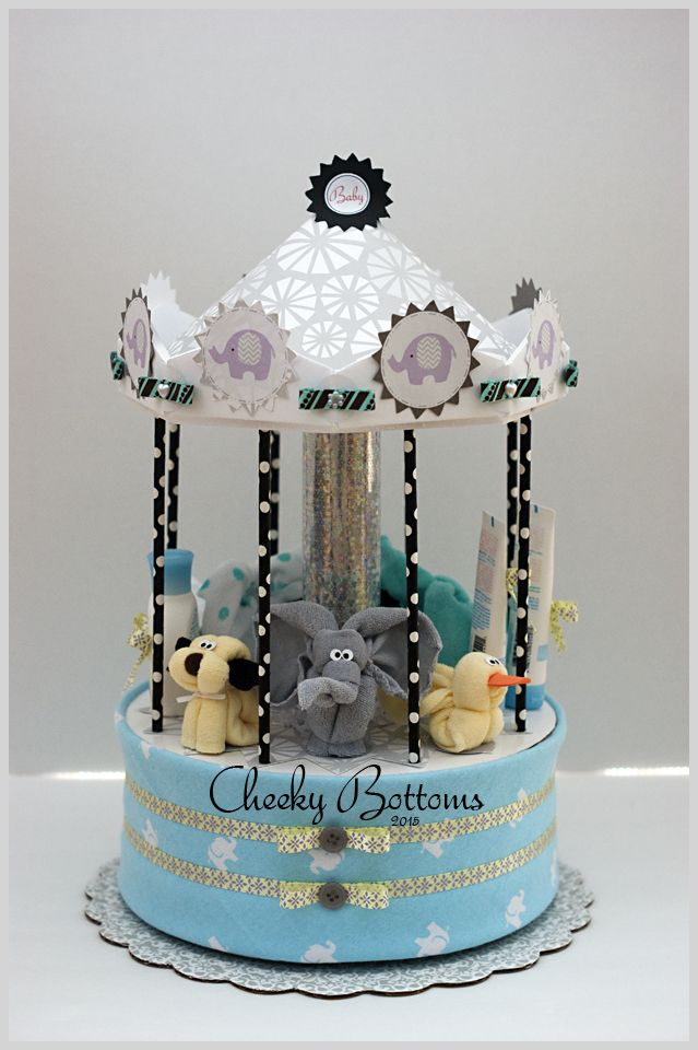 "This ""Elephant & Friends"" Carousel was featured at an former colleague's baby shower over the weekend.  Completely diaper-less, this gift is actually created with a round hat box that is hiding a few goodies for the parents-to-be (wet bag, body suit and flannel re-usable wipes). In addition, it includes one baby receiving blanket, 8 baby washcloths (three elephants, one puppy and one duck!), 2 baby spoons, 3 baby Live Clean products and 1 pair of baby booties."
