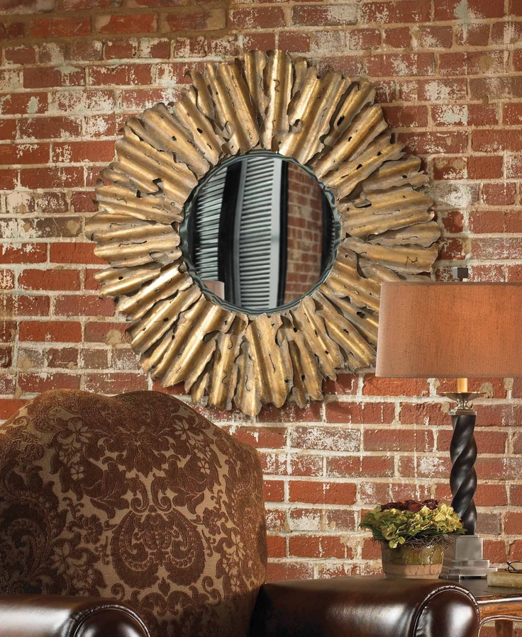 The decorative hand forged and hand hammered metal frame has an antiqued gold leaf finish with burnished edges and a light gray wash mirror has a generous