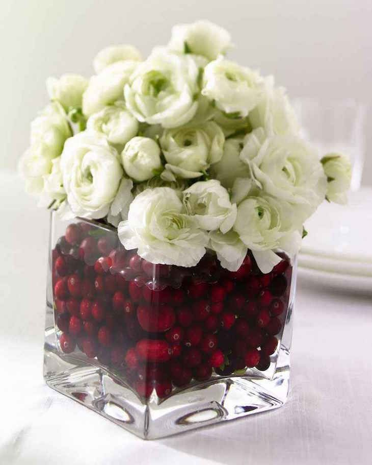 Ranunculus are prized for their heavily ruffled flowers. For a beautiful holiday arrangement, use a square glass vase, cranberries and a bouquet of white Ranunculus.