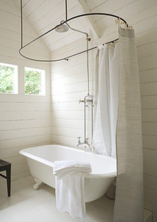Une salle de bain très épurée avec sa baignoire vintage et son rideau de douche en lin. La touche finale pour cette déco salle de bain blanche réside dans les murs en bois peints en blanc, qui donnent l'impression d'être dans une cabane. <br /><br />Photo : Gardenandmarks