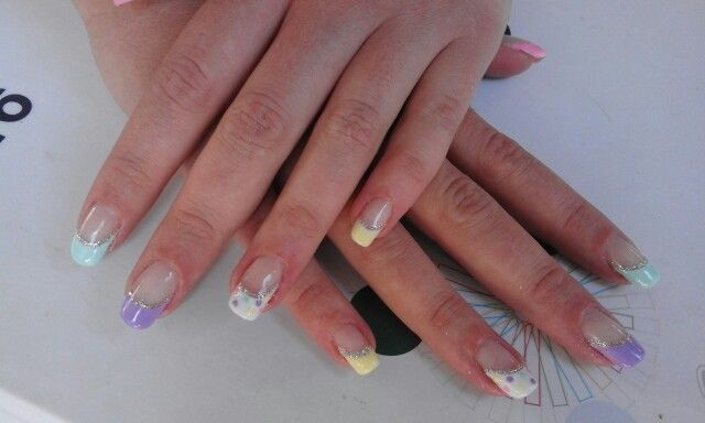 Slanted curve pastel yellow, pink, green, purple and white gel with silver glitter finished of with pastel dots on the white French