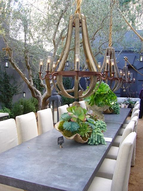 Outdoor dining space... love the succulents and big chandeliers