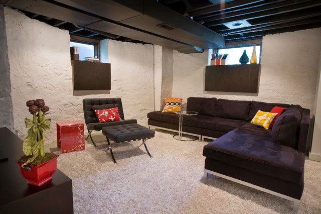 This basement has had its ceiling and beams painted in a dark color so that they recede.  Cement walls painted a neutral light shade that matches the wall-to-wall carpeting. Nice use of matching dark cloth pieces in the windows, which soften the cold edges of the opening.  Just add furniture and TV: family room. #DIY_unfinished_bssement #unfinished_basement
